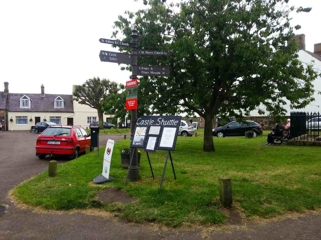 Village Green Holy Island sign points to to various attractions etc