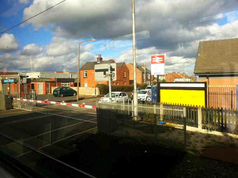 Pulling away from Bentley station on a Doncaster to Leeds Northern Rail Service crossing Church St on a Level Crossing