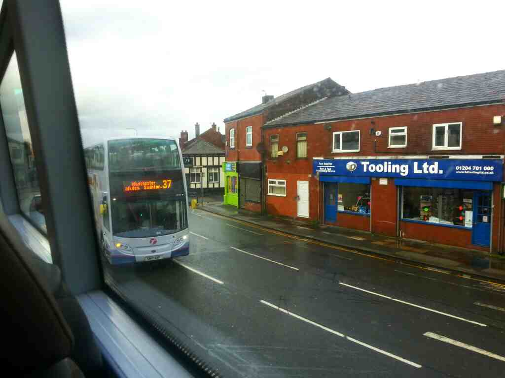 A number 37 Bolton to Manchester bus passes on Higher Market St Farnworth